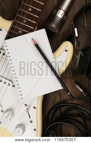 Electric guitar with headphones and microphone on wooden background
