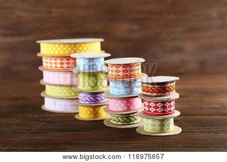 Spools of color ribbon on wooden background