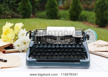 Vintage black typewriter with  old books and flowers on wooden table, outdoors