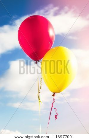 red and yellow balloons against sky with clouds, closeup