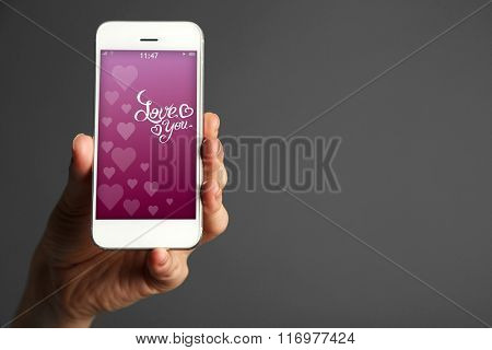 Hand holding smart phone with romantic screensaver