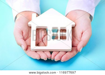 Female hands holding house on turquoise background