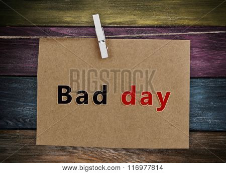 Old sheet of paper with text Bad Day hanging on rope isolated on white