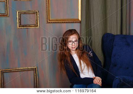 Teen Girl In Glasses Sitting In The Artist's Studio.
