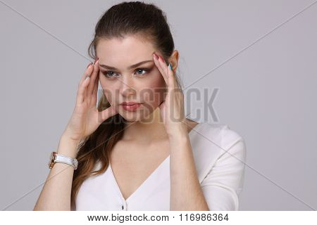 Beautiful young woman with headache touching her temples