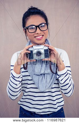 Smiling Asian woman holding camera and posing for camera