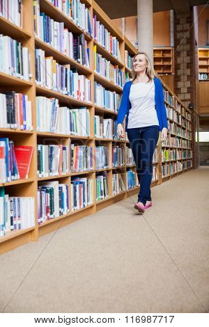 Female student walking in the library at the university