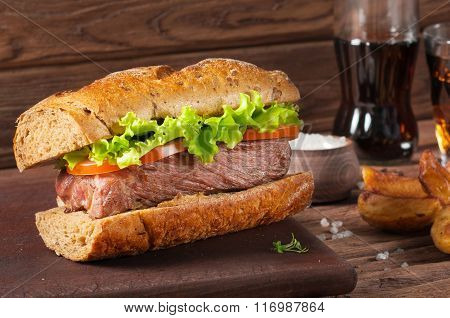 Closeup Meat Sandwich, Potatoes And Cola On Wooden Background