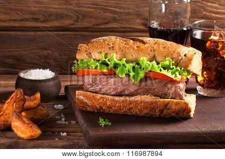 Meat Sandwich, Potatoes And Cola On Wooden Background