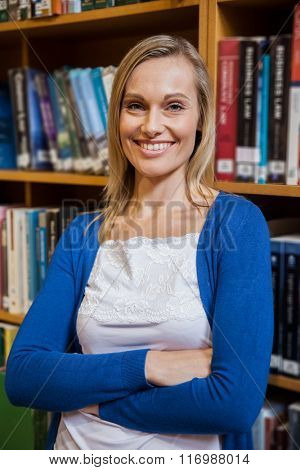 Smiling female student with arms crossed in the library at the university