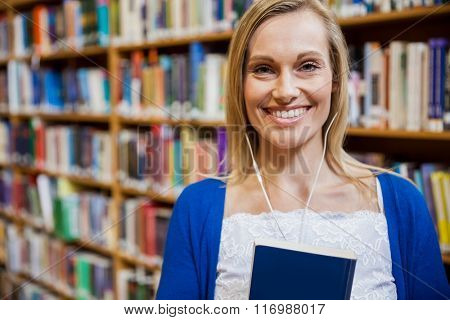 Smiling female student listening to music in the library at the university