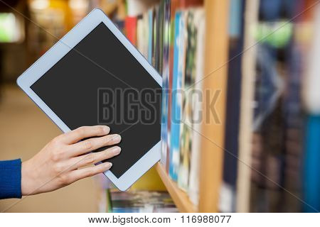 Female student tidying a tablet in a bookshelf in the library at the university