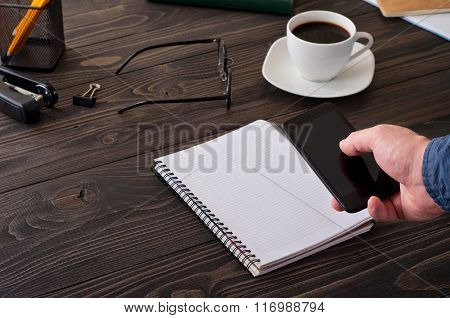 Man Working With A Smartphone For The Office Wooden Table