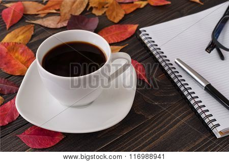 American Cup Of Coffee With Fallen Autumn Leaves And Notebook