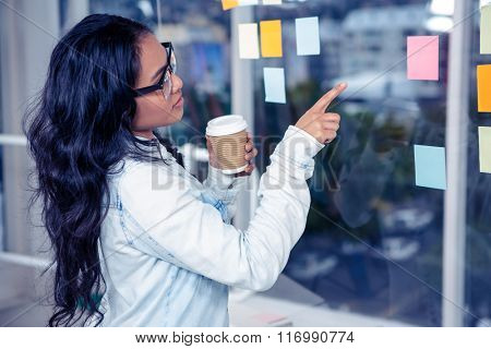 Asian woman pointing sticky note on glass wall