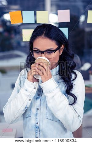 Asian woman drinking by disposable cup against glass wall