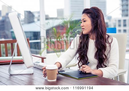 Focused Asian woman using digital board and computer in office