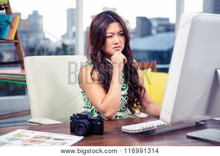 Focused Asian woman using computer with hand on chin in office