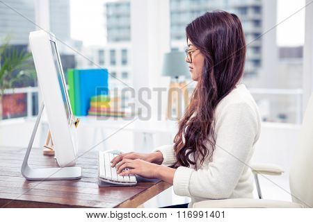 Focused Asian woman on computer in office