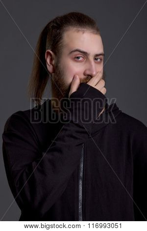 Young Man With A Beard Covers Her Mouth