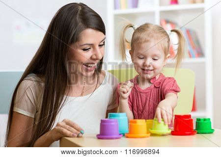 cute mother and her daughter child playing together indoor