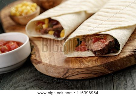burritos with beef steak, corn, black beans and salsa sauce on cutting board