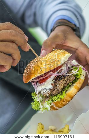 Man Holding American Hamburger With Hands. Big Delicious American Junk Hamburger With Salad, Onion,