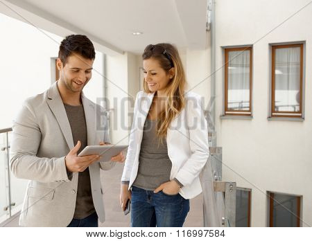 Happy couple using tablet pc in apartment house, smiling.