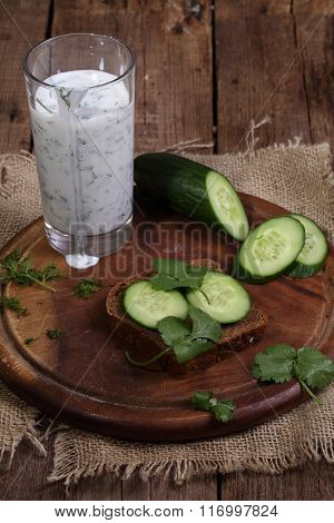 Cocktail From Kefir With A Cucumber On A Wooden Table