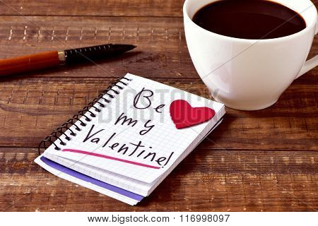 a notebook with the text be my valentine handwritten in it, a red heart, a pen and a cup of coffee on a rustic wooden table
