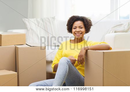 happy african woman with cardboard boxes at home