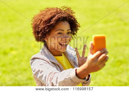 happy african woman taking selfie with smartphone