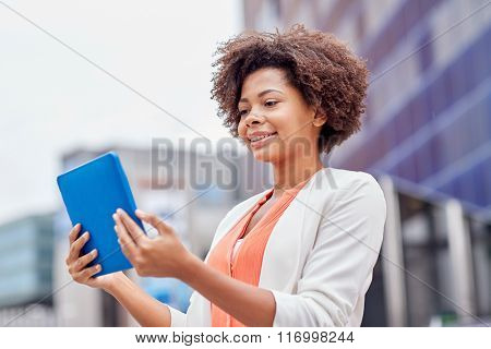 happy african businesswoman with tablet pc in city