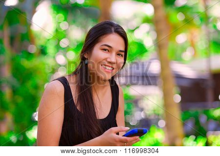 Biracial Teen Girl Using  Cellphone In Tropical Setting