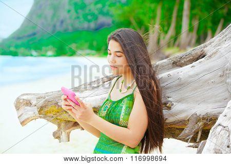 Beautiful Teen Girl Holding Cellphone , On Hawaiian Beach By Driftwood