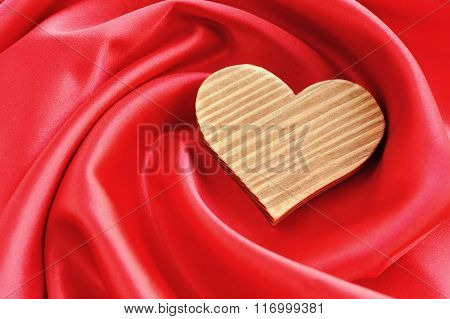 Wooden Heart On Red Satin Background
