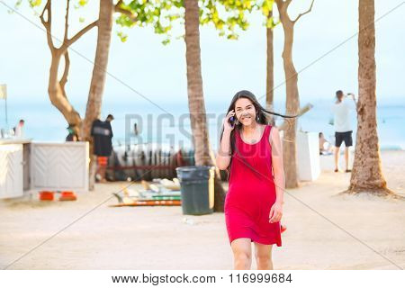 Teen In Red Dress Walking On Beach Talking On Phone