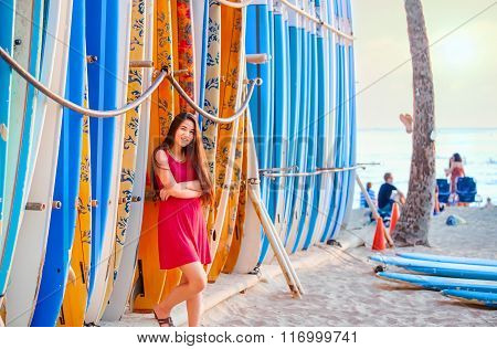 Teen Girl In Red Dress Leaning By Surfboards On Beach