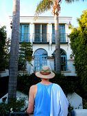 Man In Hat Looking At Grand Tropical Home