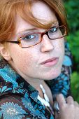 stock photo of clevage  - a beautiful redhead with glasses and a cute smile - JPG