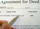 stock photo of deed  - agreement for deed document being completed showing hand pen and agreement for deed document - JPG