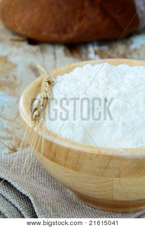 white flour in a wooden bowl with the wheat spikelet