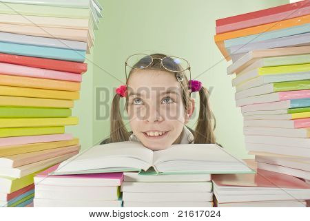 School Girl Sitting At The Table With Stacks Of Books