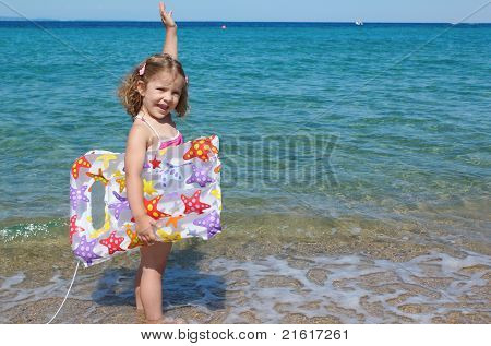happy little girl standing in the sea with hand up