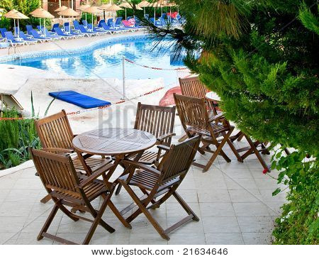 Hotel Patio With Tables And Chairs Next To Swimming Pool.