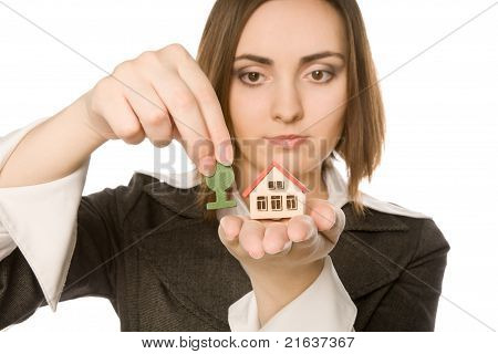 Picture Of A Young Woman Planting A Tree (focus On House)