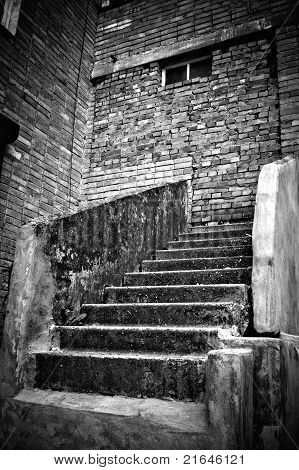 The Strange Staircase Leading Into Brick Wall. Black And White Photo