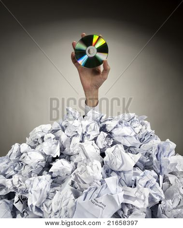 Hand With Cd Reaches Out From Heap Of Papers