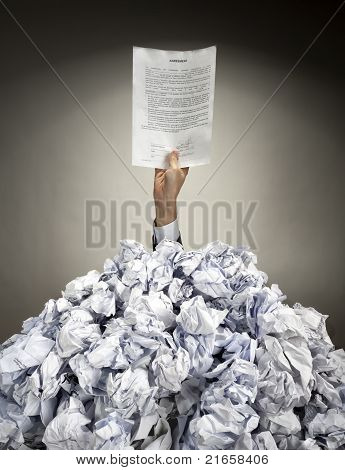 Hand With Agreement Reaches Out From Heap Of Papers