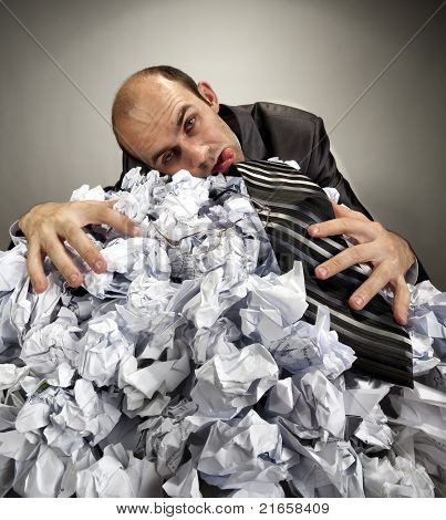 Exhausted Depressive Businessman Laying On Crumpled Papers